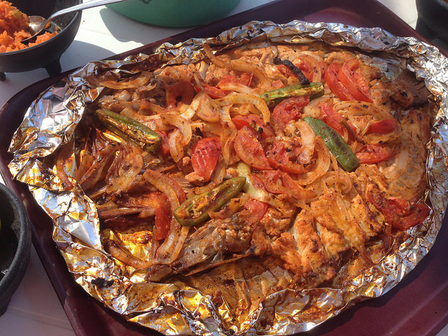 Whole fish cooled with tomatoes. onions, peppers